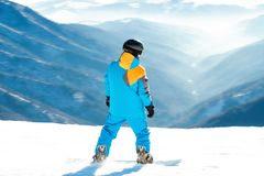 Male snowboarder sliding at the mountain slope. Young male snowboarder sliding fast at the very top of a mountain slope Royalty Free Stock Photography
