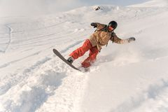 Male snowboarder in sportswear and helmet riding down the powder. Snow hill on the sunny day Stock Photography