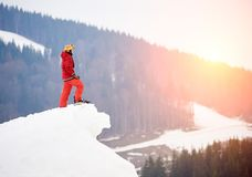 Male snowboarder standing on the top of the snowy hill with snowboard, enjoying sunset. Skiing and snowboarding concept Royalty Free Stock Photos
