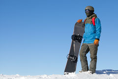 Male snowboarder taking a look at landscape at the top of mountains with blue sky on background Stock Images