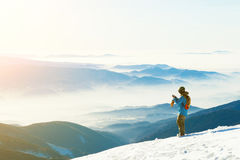 Male snowboarder taking photo of the beautiful landscape with sun-set. Snowboarder taking photo of the beautiful landscape and sun-set from the very top of a Royalty Free Stock Photo