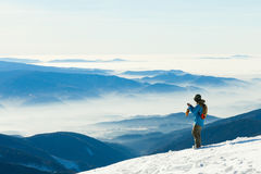Male snowboarder taking photo of the beautiful landscape from the very top of a mountain Royalty Free Stock Photos