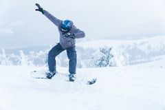 Male snowboarding snowboard jump. go in the mountains on Snow Mountain winter snowboarding stock images