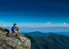 Male Soaks in the View of the Dramatic Ridge Below. In summer Royalty Free Stock Photo