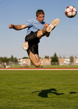 Male soccer. Athletic male in the air kicking a soccer ball royalty free stock photography