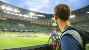 Male soccer fan watching match from tribune at stadium, supporting national team. Stock footage stock video