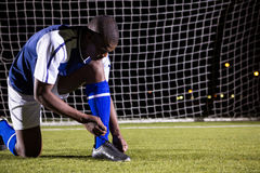 Male soccer player tying shoelace on field Royalty Free Stock Photo