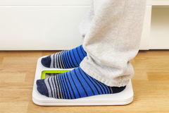 Male in socks and lounge pants on digital scale Royalty Free Stock Image