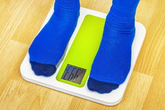 Male in socks with overweight standing on the scale. In room stock photography