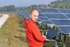 Male solar panel engineer at work place. Male engineer at work place, solar panels plant industy in background Royalty Free Stock Photography