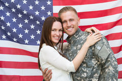 Male Soldier With His Wife In Front Of American Flag. Portrait Of Young Male Soldier With His Wife In Front Of American Flag Royalty Free Stock Photography