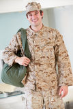Male Soldier With Kit Bag Home For Leave. Smiling To Camera Stock Image