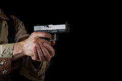 Male soldier pointing his weapon in darkness. Close up horizontal image of pistol, pointing sideways into darkness, with armed male soldier in background. Focus Stock Photo