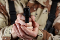 Male soldier pointing his weapon forward. Close up horizontal image of pistol, pointing forward, with armed male soldier in background. Focus on front part of Royalty Free Stock Image
