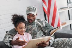 Male soldier reading book to. His daughter Royalty Free Stock Photo