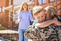 Male soldier reunited with his family outdoors. Military service. Male soldier hugging with his son outdoors. Military service royalty free stock photos