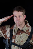 Male Soldier saluting while under arms. Vertical image of military male soldier saluting while armed with black background Royalty Free Stock Images