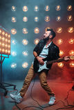 Male solo guitarist with electro guitar. On the stage with the decorations of lights. Music entertainment. Bearded musican song performing Stock Photography