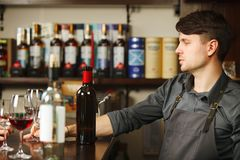 Male sommelier at bar counter closeup of alcohol drinks bottles. And glasses with rum and wine, thoughtful bartender at work place on background of shelf with Stock Image