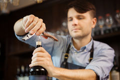 Male sommelier open wine bottle with corkscrew. Waiter with bottle of alcohol beverage and bottle-screw in hands. Bartender concentrated on uncork of elite Stock Image