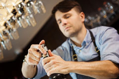 Male sommelier open wine bottle with corkscrew. Waiter with bottle of alcohol beverage and bottle-screw in hands. Bartender concentrated on uncork of elite Royalty Free Stock Image