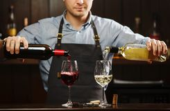 Male sommelier pouring red and white wine into long-stemmed wineglasses. Waiter with two bottles of alcohol beverage. Bartender at bar counter Stock Photos