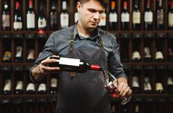 Male sommelier pouring red wine into long-stemmed wineglasses. Waiter with bottle of alcohol beverage. Bartender on background of shelves with bottles in royalty free stock photos