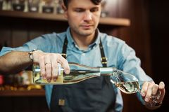 Male sommelier pouring white wine into long-stemmed wineglasses. Royalty Free Stock Images