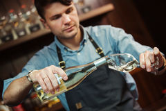 Male sommelier pouring white wine into long-stemmed wineglasses. Royalty Free Stock Photos