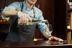 Male sommelier pouring white wine into long-stemmed wineglasses. Stock Image