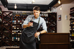 Male sommelier tasting red wine in cellar. Professional degustation expert. Appreciate quality of wine. Winemaker with bocal of alcohol drink and bottle in Royalty Free Stock Photography