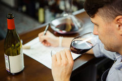 Male sommelier tasting red wine and making notes at bar counter. Bottle of wine nearby. Professional expert appreciates quality of alcoholic beverage Stock Photography