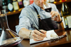 Male sommelier tasting red wine and making notes at bar counter Stock Photo