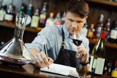 Male sommelier tasting red wine and making notes at bar counter. Bottle of wine nearby. Professional expert appreciates quality of alcoholic beverage Royalty Free Stock Photos