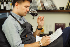 Male sommelier tasting red wine and making notes. Profession in winemaking. Man waiter with long-stemmed wineglass sitting in chair and drinking alcohol Royalty Free Stock Photography