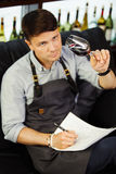 Male sommelier tasting red wine and making notes. Profession in winemaking. Stock Photos