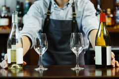 Male sommeliers holds white and red wine. The waiter with two bottles of liquor. The bartender behind the bar Stock Photography
