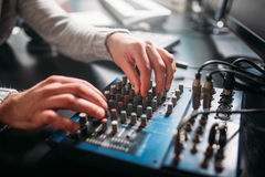 Male sound engineer hands on volume control panel. Digital music record studio. Professional audio engineering royalty free stock photography