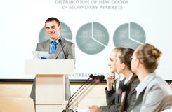 Male speaker. Man speaking at conferences, keeps records, stands behind a podium Stock Images