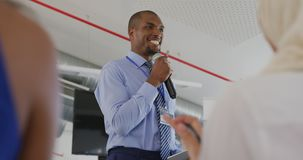 Male speaker addressing applauding audience at a business seminar. Over the shoulder view of a young African American businessman standing in front row of the stock footage