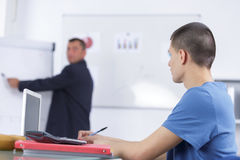 Male speaker in front whiteboard screen giving presentation. Male speaker in front of whiteboard screen giving presentation Stock Images