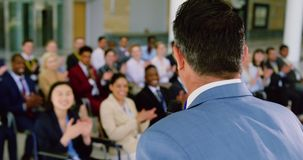Male speaker speaks in a business seminar 4k. Side view of caucasian male speaker speaks in a business seminar. Business people applauding him in a seminar 4k stock video
