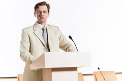 Male speaker. Stands behind a podium on the stage and looking into the hall Royalty Free Stock Photos