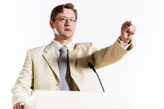Male speaker. Stands behind a podium on the stage and looking into the hall Stock Photo