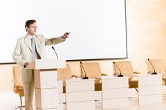 Male speaker. Stands behind a podium on the stage and looking into the hall Stock Image