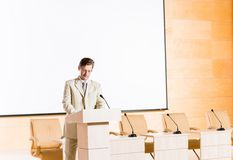 Male speaker. Stands behind a podium on the stage and looking into the hall Stock Photos