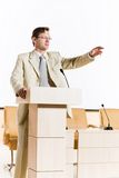 Male speaker. Stands behind a podium on the stage and looking into the hall Royalty Free Stock Image