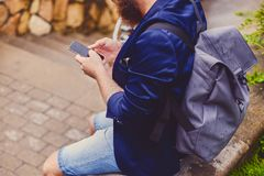 Male speaking by a smartphone. Back view. Traveller male speaking by a smartphone. Back view royalty free stock image