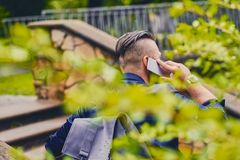 Male speaking by a smartphone. Back view. Traveller male speaking by a smartphone. Back view royalty free stock photography