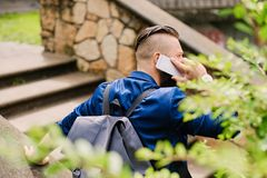 Male speaking by a smartphone. Back view. Traveller male speaking by a smartphone. Back view royalty free stock images